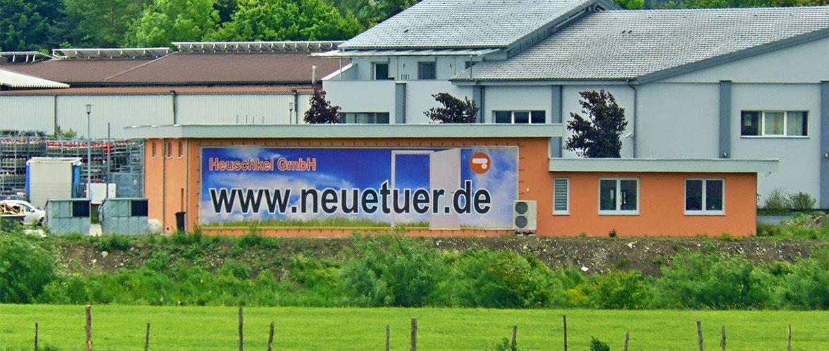 Ihr Wegweiser zu uns - schon weit sichtbar. Heuschkel GmbH. Boden. Türen. Wand. Aus einer Hand!